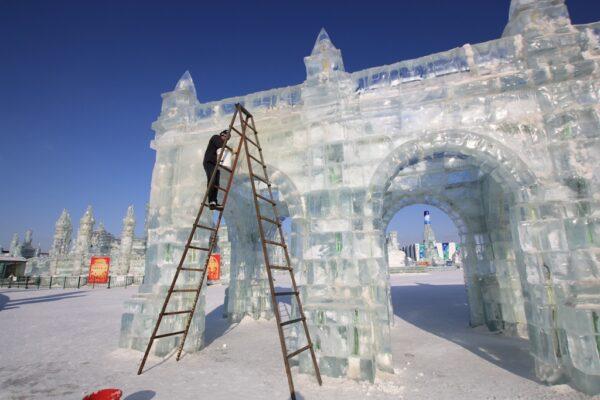 Einsturzgefahr: Arbeiter kontrolliert die Festigkeit der Eisbauten.