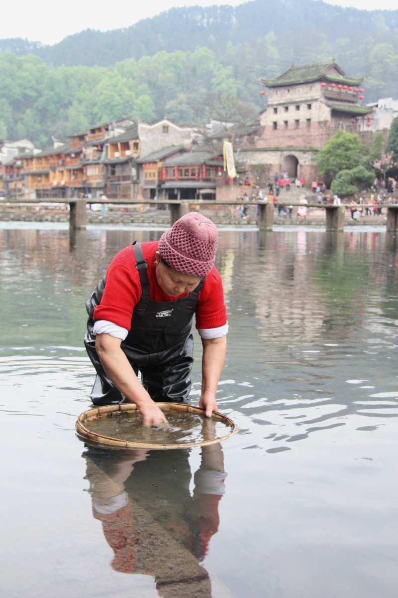 Aus den Flusskrevetten, welche diese Frau fängt, entsteht in Fenghuang ein salziger Snack.