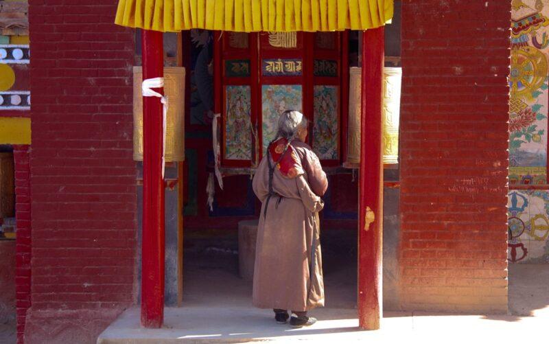 Eine Tibeterin betätigt im Kloster von Tongren eine Gebetsmühle.
